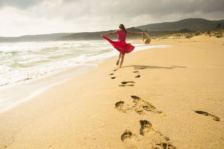 Beautiful energetic young woman running freely on the beach photo