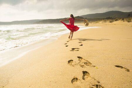 donna che balla: Bella donna giovane energica esecuzione liberamente sulla spiaggia