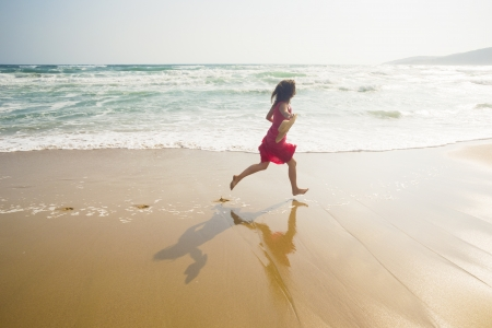radiant light: Happy young woman running along the beach
