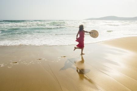 Joyful young woman running along the sunny beach photo