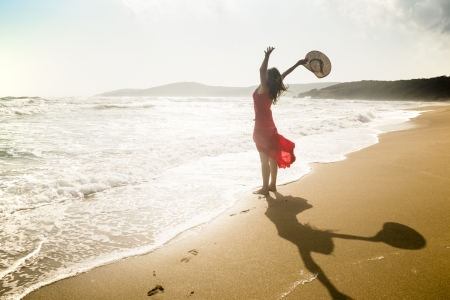 Happy young woman raises her arms towards the sea Stock Photo