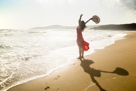 Heureuse jeune femme lève les bras vers la mer. Banque d'images - 16117144