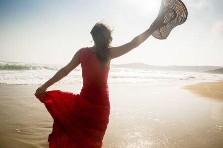 radiant light: Beautiful young woman raises her hat on a sunny beach