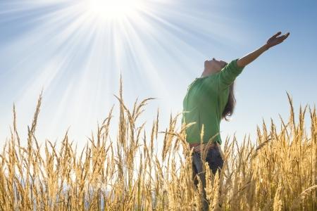 Bonne jeune fille en levant les bras avec bonheur et joie dans l'herbe haute sur une belle journée ensoleillée Banque d'images