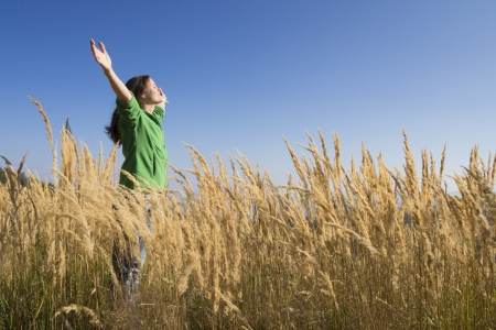 Happy young girl raising her arms with bliss and joy in the tall grass on a beautiful sunny day photo