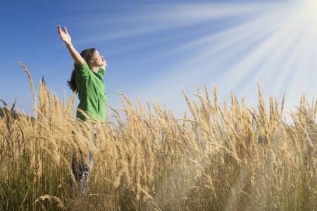 Gelukkig jong meisje de opvoeding van haar armen met gelukzaligheid en vreugde in het hoge gras op een mooie zonnige dag