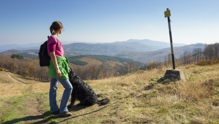 causasian: Slim young girl walking in the mountains with her dog looking at a singpost