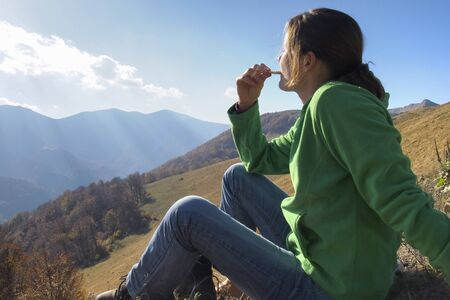 Girl resting on the grass in the mountains enjoying the taste of a bisciut in the warm light of the sun photo