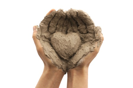 Female hands on a white background holding a heart made out of clay