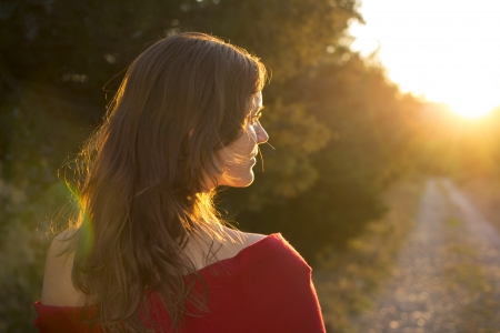 Beautiful young girl walking on a country road towards the light of the setting sun photo