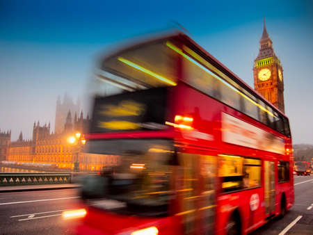 london tower bridge: Big Ben with the Houses Of Parliament and a red double-decker bus passing at dusk Stock Photo