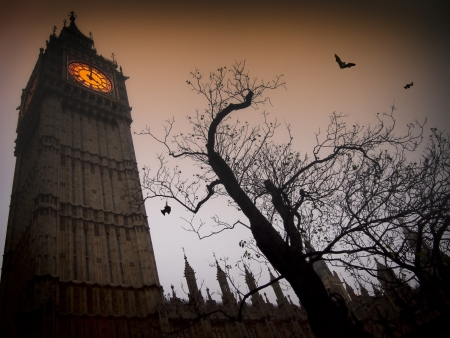 The spooky clock tower of Westminster with a bare tree and flying bats 版權商用圖片