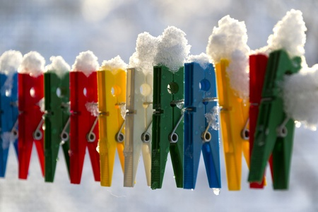 queueing: Washing line with a row of colorful pegs covered with snow queued in a row