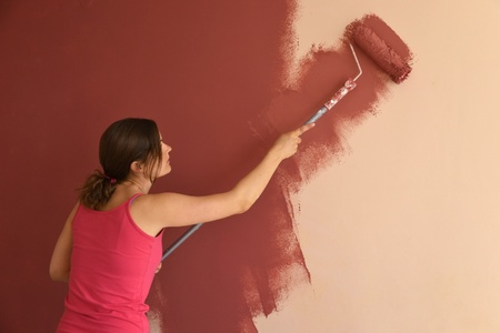 Beautiful young woman in causal clothes painting a wall with red paint and a roller photo