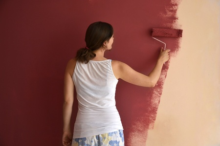 causal: Beautiful young woman in causal clothes painting a wall with red paint and a roller