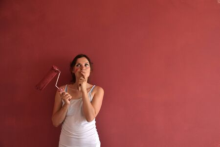 Beautiful young woman in causal clothes thinking about the result of the work she has done painting a wall with red paint and a roller photo