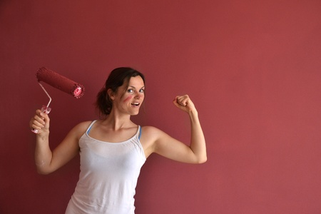 empowered: Beautiful young woman in causal clothes showing muscles and feeling empowered  and happy by the job she had done painting a wall with red paint and a roller