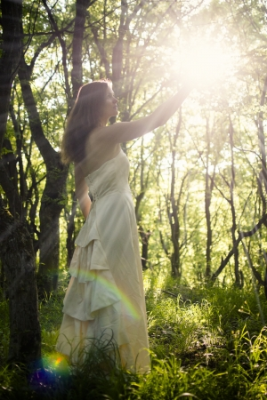 Beautiful young woman wearing elegant white dress in the forest holding the sunlight with rays of light beaming through photo