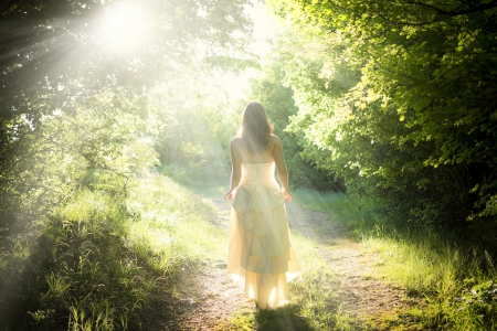 Beautiful young woman wearing elegant white dress walking on a forest path with rays of sunlight beaming through the leaves of the trees Stock Photo