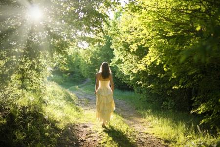 Schöne junge Frau trägt eleganten weißen Kleid zu Fuß auf einem Waldweg mit Sonnenstrahlen strahlend durch die Blätter der Bäume