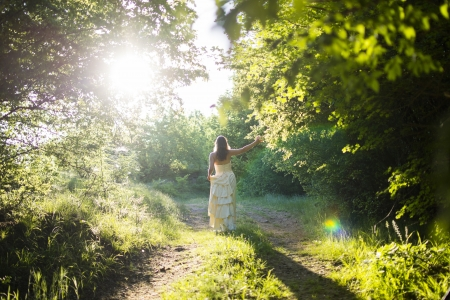 Beautiful young woman wearing elegant white dress walking on a forest path with rays of sunlight beaming through the leaves of the trees photo