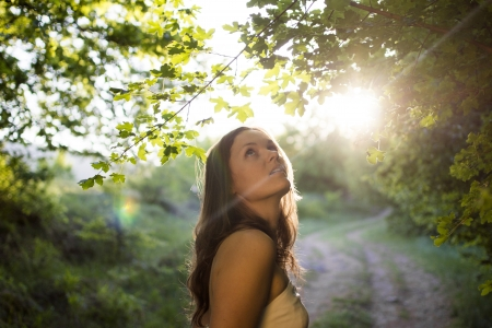 Beautiful young woman wearing elegant white dress looking amazed by the forest with rays of sunlight beaming throught the leaves of the trees