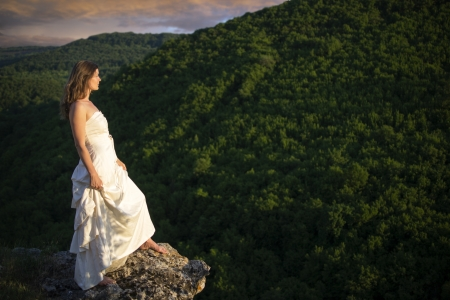 Beautiful young woman wearing elegant white dress standing on a rock overlooking the great expance of forests and mountains