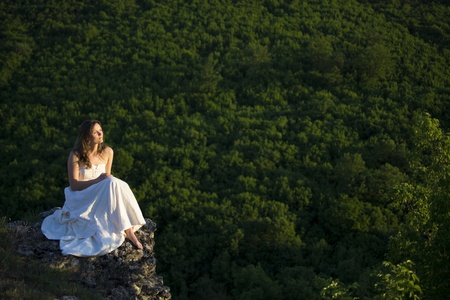 Beautiful young woman wearing elegant white dress sitting on a rock overlooking the great expance of forests and mountains photo