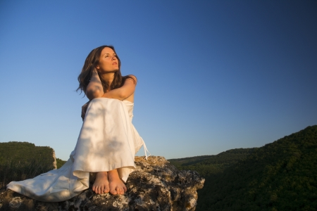Beautiful young woman wearing elegant white dress sitting on a rock overlooking the forests and mountains