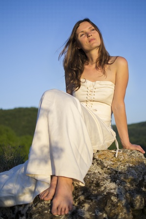 Beautiful young woman wearing elegant white dress sitting on a rock surrounded by green forest Stock Photo - 21498339