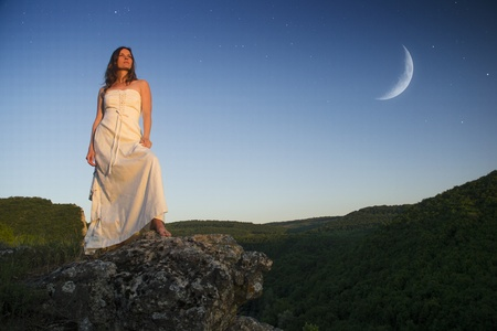 Beautiful young woman wearing elegant white dress standing on a rock overlooking the great expance of forests and mountains under blue sky with moon and stars