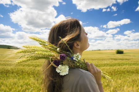 Beautiful young woman in holding a bunch of wild flowers enjoying the clear sunny day in a field of wheat