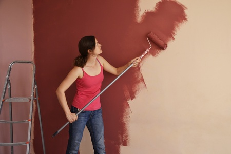 capable: Beautiful young woman in causal clothes painting a wall with red paint and a roller