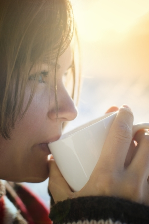 Beautiful young woman drinking hot drink outside on a sunny cold winter morning