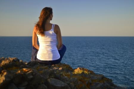 Beautiful young woman sitting on a rock contemplating the blue evening sea.