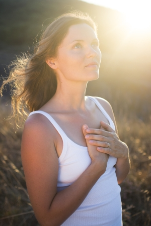 woman chest: Beautiful young woman with her hands on her chest looking gratefully towards the sky. Stock Photo