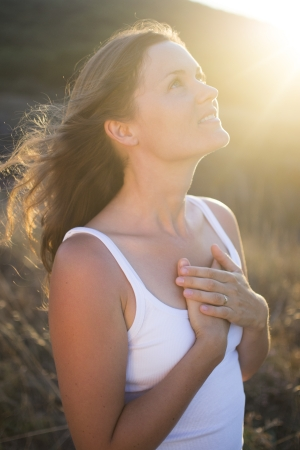 happy: Beautiful young woman with her hands on her chest looking gratefully towards the sky. Stock Photo