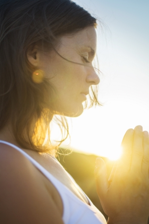 Beautiful young woman in silent meditation and prayer connected in the spirit with the universal love of God. photo