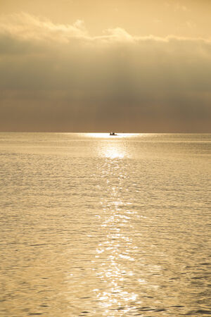 horizon over water: Fishermen going out with their boat with the sunrise at the island of Thassos, Greece.
