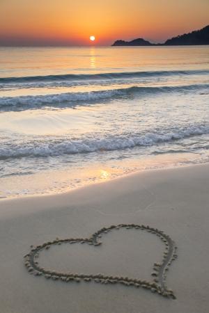 En forme de coeur dessiné sur une plage de sable au lever du soleil sur la belle île de Thassos, Grèce. Banque d'images - 25204432