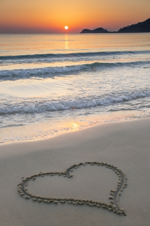 Heart shape drawn on a  sandy beach at sunrise on the beautiful island of Thassos, Greece. photo