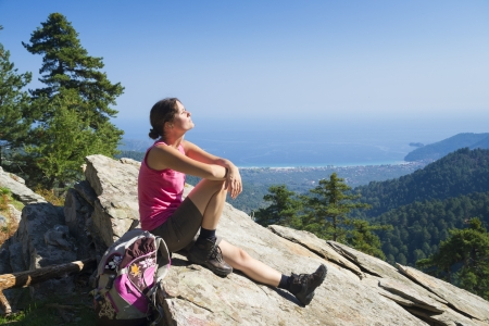 Beautiful fit young woman hiking up a mountain and enjoying the panoramic view on the island of Thassos, Greece. 版權商用圖片
