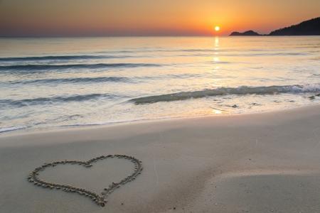 Heart shape drawn on a  sandy beach at sunrise on the beautiful island of Thassos, Greece.