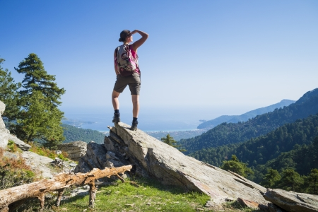 Beautiful fit young woman hiking up a mountain and enjoying the panoramic view on the island of Thassos, Greece. photo