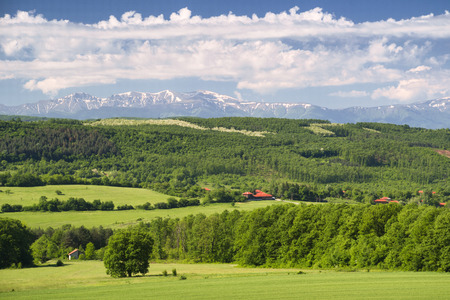 color range: Green spring fields, forest and a small village with high mountain tops still covered with snow on a clear, sunny day in Bulgaria.