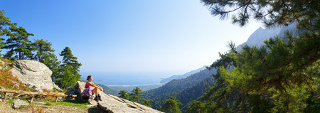 panorama view: Beautiful fit young woman taking a break and enjoying the view of the mountain at the island of Thassos, Greece.