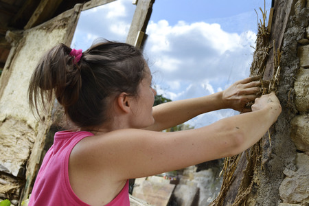 mud house: Young female plastering a old stone building with natural materials - clay, sand and straw. Stock Photo