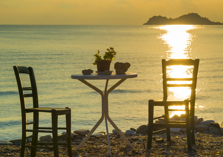 Two empty chairs and a table standing lonely in the peaceful sunshine of a mediterranean morning by the sea.