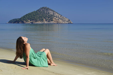 Beautiful young woman enjoying the sunshine and pristine nature at Paradise beach on the island of Thassos, Greece photo