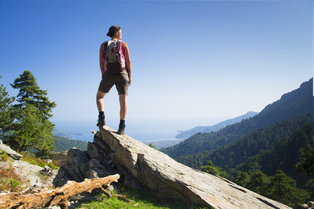 top of the world: Beautiful fit young woman hiking up a mountain and enjoying the panoramic view on the island of Thassos, Greece. Stock Photo